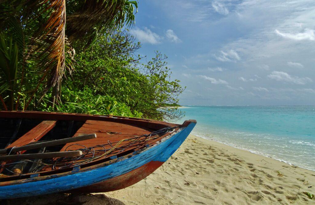 Een bootje ligt afgelegen op het strand van Feridhoo waar we backpacken in de Malediven.